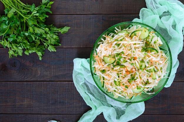 Диетический салат с капустой, огурцом, морковью, зеленью. сочный весенний салат со свежими овощами на деревянном столе. правильное питание. вид сверху.