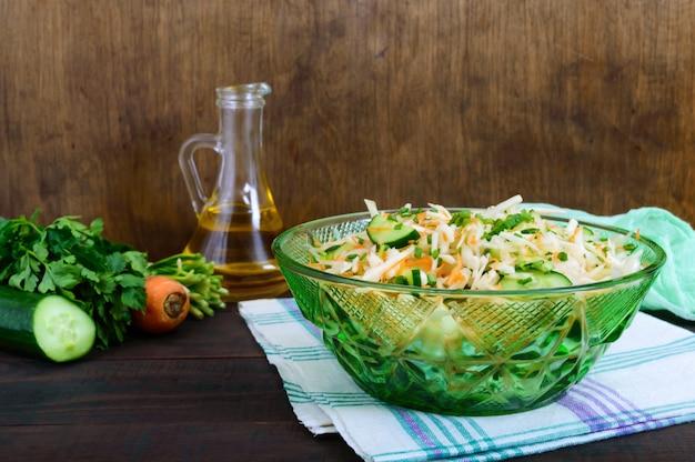 キャベツ、キュウリ、ニンジン、野菜のサラダ。木製のテーブルに新鮮な野菜とジューシーな春のサラダ。適切な栄養。