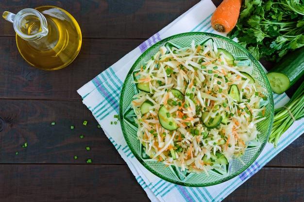 Диетический салат с капустой, огурцом, морковью, зеленью. сочный весенний салат со свежими овощами на деревянном столе. правильное питание.