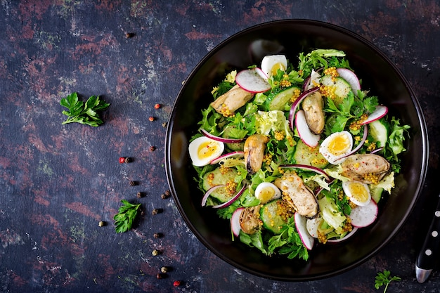 Dietary salad with mussels, quail eggs, cucumbers, radish and lettuce. healthy food. seafood salad. top view. flat lay.