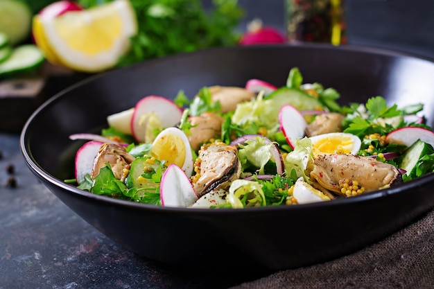 Dietary salad with mussels, quail eggs, cucumbers, radish and lettuce. healthy food. seafood salad.