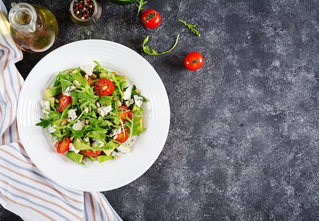 Dietary salad with tomatoes, blue cheese, avocado, arugula and pine nuts.