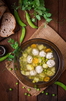 Dietary soup with chicken meatballs and green peas in a glass bowl on a wooden table.