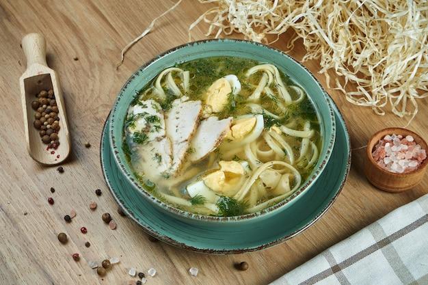 닭고기, 야채와 파 슬 리 블루 세라믹 그릇에 나무 테이블에 재료로 구성식이 수프. 상위 뷰 맛있는 수프. 평평한 음식