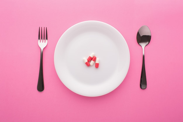 Dietary supplement on plate with fork and spoon on pink, top view