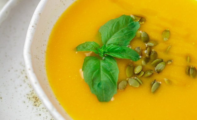 Dietary vegetarian pumpkin cream soup puree with olive oil, seeds and basil