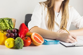 Dietician's hand writing on clipboard with healthy food on desk