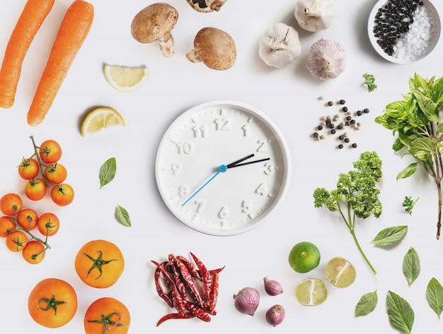 ダイエットと健康的な食事。食品成分、野菜、ハーブで囲まれた時計