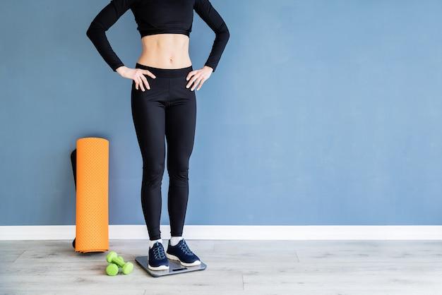 다이어트와 체중 감소. 저울에 서있는 검은 스포츠 옷 여자