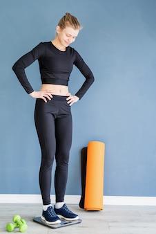 다이어트와 체중 감소. 저울에 서있는 검은 스포츠 옷에 젊은 행복 한 여자