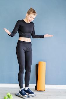다이어트와 체중 감소. 저울에 서있는 검은 스포츠 옷에 젊은 놀란 된 여자
