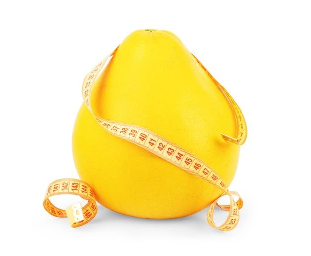 Концепция диеты. фрукты памела крупным планом и яблоки с рулеткой