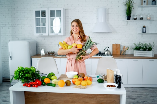 Dieting concept. diet. beautiful young woman near table in the kitchen with healthy food. fruits and vegetables.