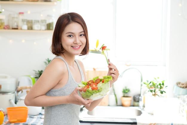 ダイエットの概念。健康食品。新鮮な野菜サラダを食べる美しい若いアジアの女性。ゆるい体重の概念