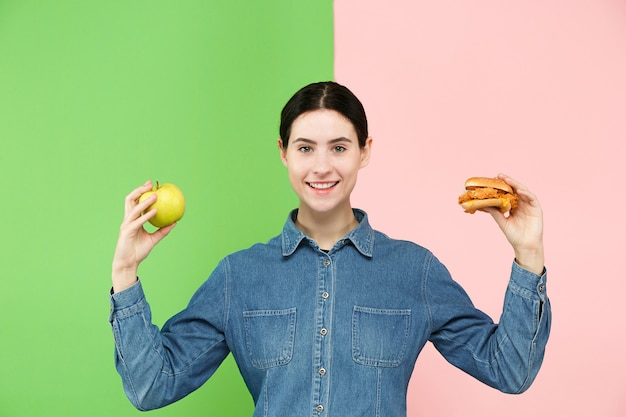 다이어트 개념. 건강에 좋은 유용한 음식. 스튜디오에서 과일과 건강에 해로운 패스트 푸드 사이에서 선택하는 아름 다운 젊은 여자. 인간의 감정과 비교 개념