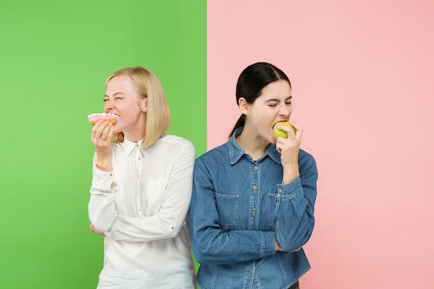 다이어트 개념. 건강에 좋은 유용한 음식. 스튜디오에서 과일과 건강에 해로운 케이크 사이에서 선택하는 아름 다운 젊은 여성. 인간의 감정과 비교 개념