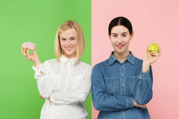 다이어트 개념. 건강에 좋은 유용한 음식. 스튜디오에서 과일과 건강에 해로운 케이크 사이에서 선택하는 아름 다운 젊은 여성.