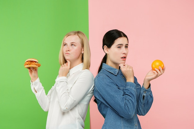 다이어트 개념. 건강에 좋은 유용한 음식. 스튜디오에서 과일과 건강에 해로운 패스트 푸드 사이에서 선택하는 아름 다운 젊은 여성. 인간의 감정과 비교 개념