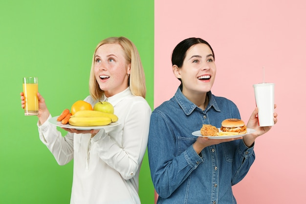 ダイエットの概念。健康に役立つ食品。スタジオで果物と不健康なファーストフードのどちらかを選ぶ美しい若い女性。人間の感情と比較の概念