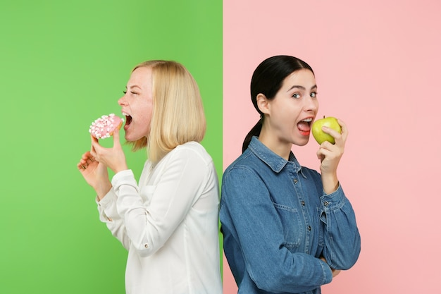 Dieting concept. healthy useful food. beautiful young women choosing between fruits and unhealthy cake at studio.