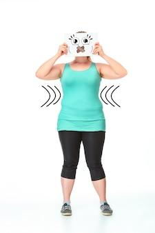 ダイエットの概念。白いスタジオの背景に描画と紙のシートで彼女の口を閉じて完全に成長している太った女の子の肖像画