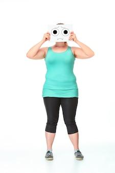 ダイエットの概念。白いスタジオの背景に描画された紙のシートで彼女の口を閉じて完全に成長している太った女の子の肖像画