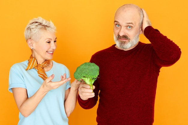 Dieta, cibo, salute, prodotti biologici e concetto di vegetarismo. uomo anziano frustrato che guarda l'obbiettivo con espressione facciale triste, tenendo broccoli disgustosi, sua moglie gli fa mangiare verdure