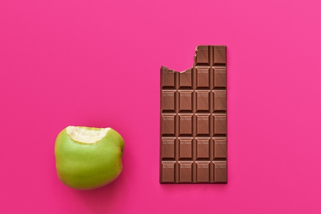 Dieting or good health concept. choice between healthy food such as fresh apple or sweet chocolate