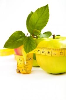 ダイエット。葉と白いスペースで隔離のテープで緑、黄色のリンゴ