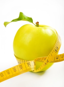 На диете. зеленое, желтое яблоко с листом и лентой на белом фоне
