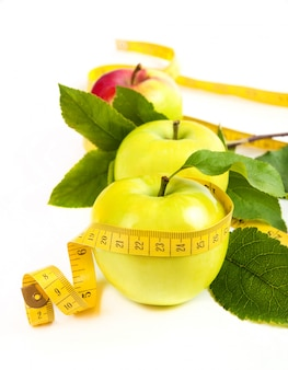 Dieting. green, yellow apple with leaf and tape isolated on a white space