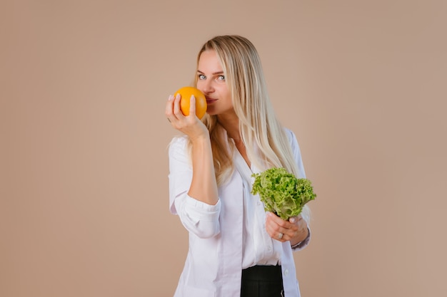 The dietitian is holding fruits and vegetables