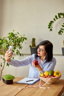 健康的な食事についての彼女のvlogをスマートフォンで記録している栄養士の女性