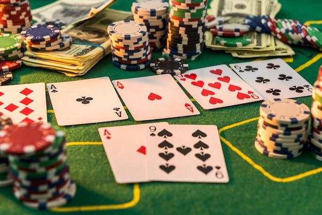 녹색 카지노 테이블에 카드 놀이와 미국 달러가있는 비용 포커 칩에 대해 다릅니다. 도박