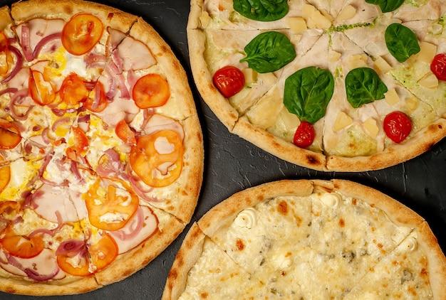 コンクリートの背景に異なる3つのピザピザ