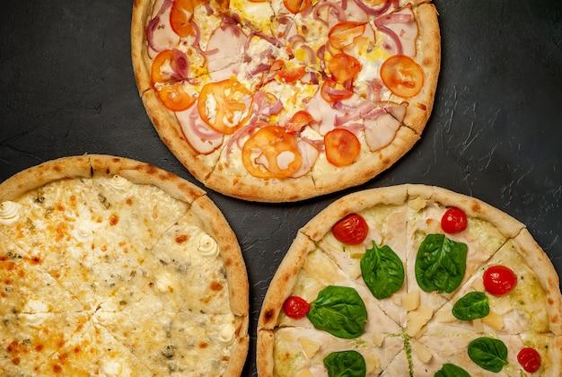 Разные 3 пиццы пиццы на бетонном фоне