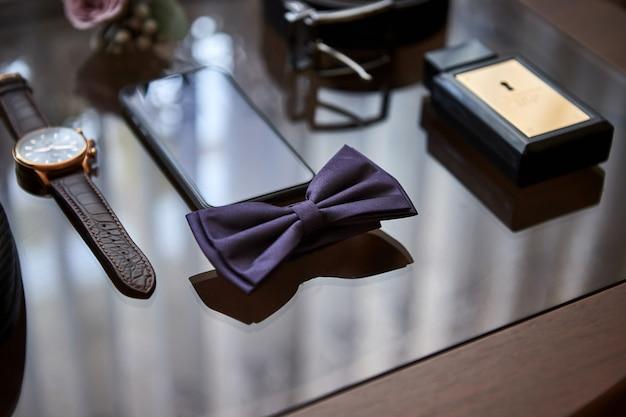 На деревянной поверхности лежат разные аксессуары бизнесмена для создания стиля в народе.