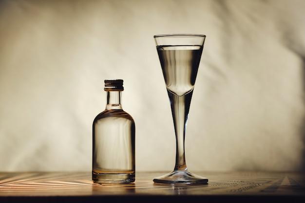 明るい背景のテーブルには、さまざまなアルコールボトルがあります。