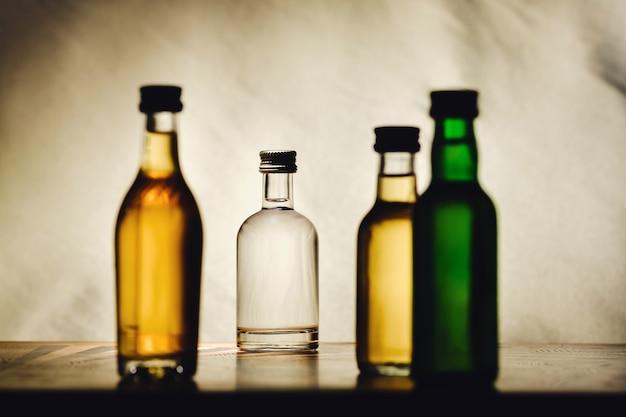 밝은 배경에 다른 알코올 병이 테이블에 있습니다.