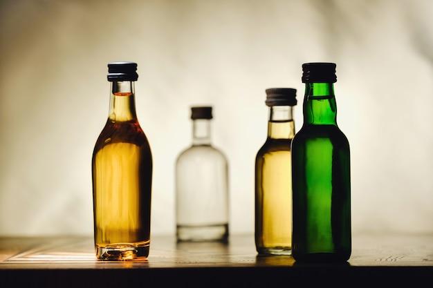 다른 알코올 병이 밝은 배경의 탁자 위에 있습니다