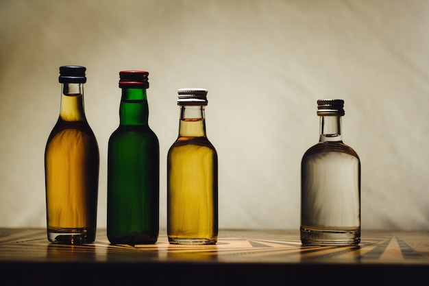 Different alcohol bottles are on the table on a light