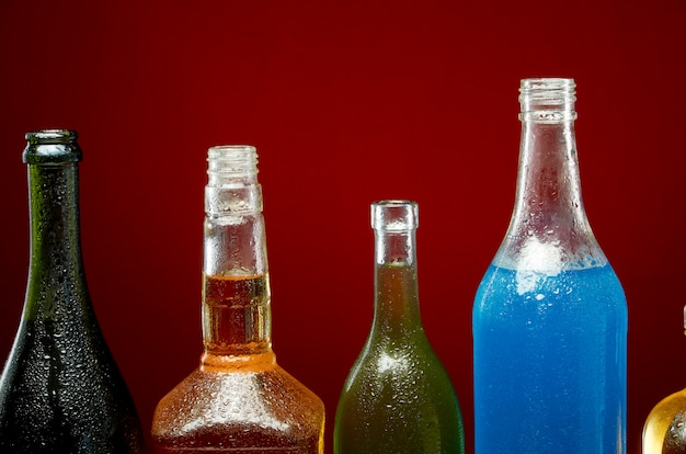 Different alcoholic drinks in transparent bottles on red