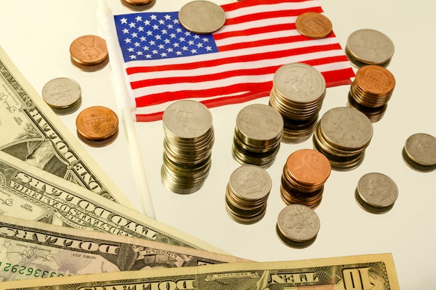 Different american coins and banknotes and the american flag lie on the reflecting surface.