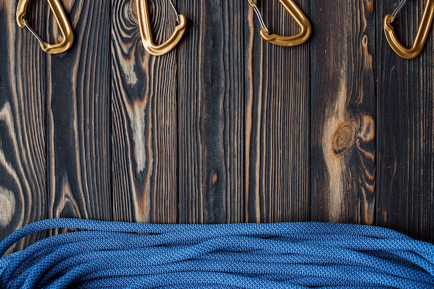 Другой угол зрения. изолированное альпинистское снаряжение. часть карабина, лежащая на деревянном столе.