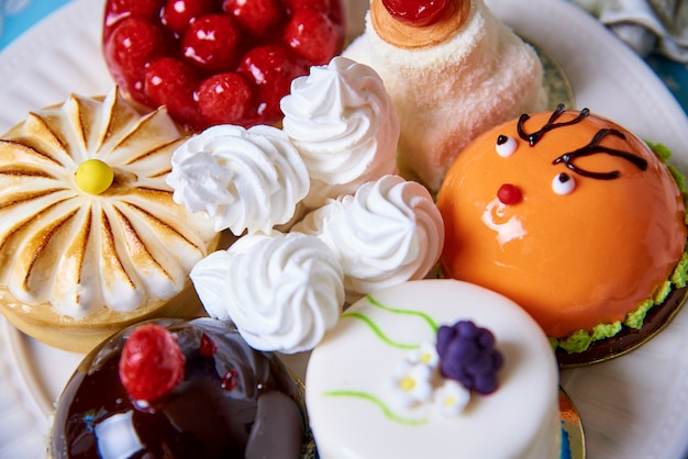 Different appetizing tasty cakes on a plate close-up.