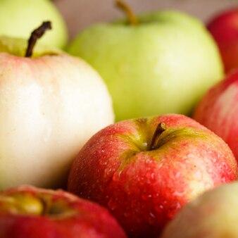 庭の木製のテーブルに別のリンゴ