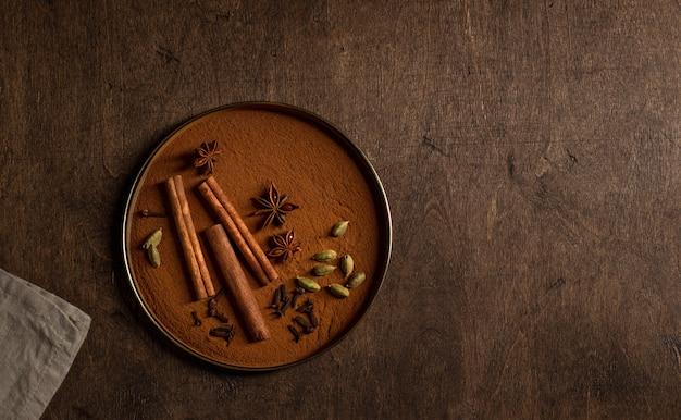 プレートの異なる芳香族スパイス。カルダモン、シナモン、クローブ、スターアニス。木製の背景、トップビュー、コピースペース