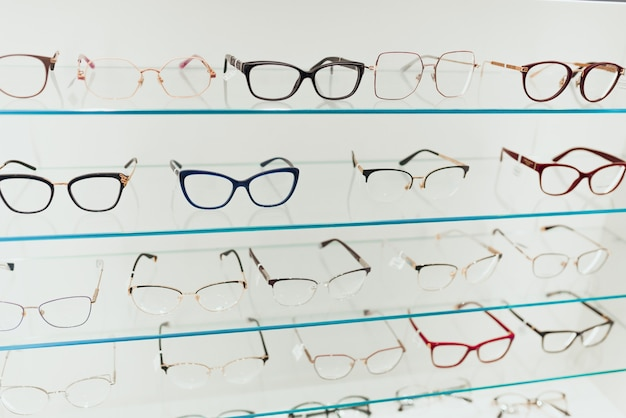 Различный ассортимент оправ для очков на дисплейных панелях в магазине оптики