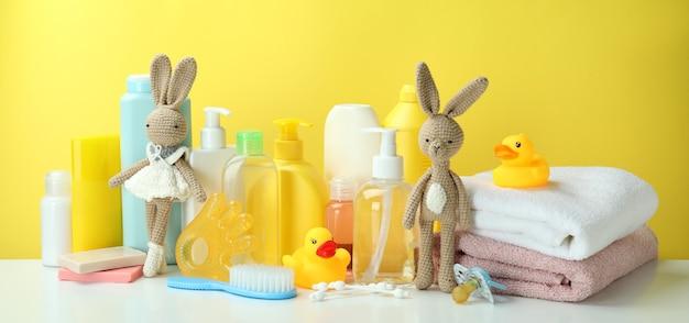 Различные аксессуары детской гигиены на желтом фоне