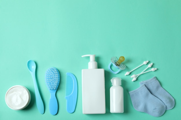 Different baby hygiene accessories on mint background